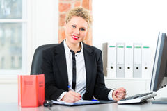 Lawyer in office with law book working on desk. Young female lawyer working in her office with a typical law book and writing in a document stock images