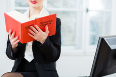 Lawyer in office reading law book. Young female lawyer working n her office reading in a typical law book royalty free stock photos
