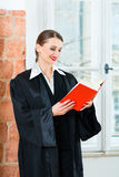Lawyer in office reading law book Stock Image