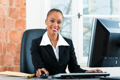 Lawyer in office sitting on the computer. Young female lawyer or paralegal working in her office on a Computer or Pc stock photo