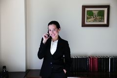 Lawyer at office talking on phone. Happy female lawyer at office talking on phone smiling royalty free stock photo
