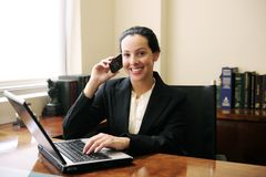 Lawyer on phone with laptop. Female lawyer at office talking on phone and using laptop royalty free stock photo