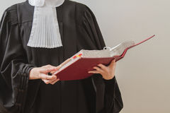 Lawyer reading. Canadian lawyer in toga, reading from a red law book Royalty Free Stock Photography