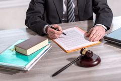 Lawyer reading legal document (Lorem ipsum text used). Lawyer working on legal document (Lorem ipsum text used stock photo
