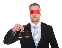 Lawyer with scales of justice wearing a blindfold. Lawyer or judge with the scales of justice in his hand wearing a blindfold  conceptual of impartiality and Royalty Free Stock Images