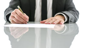 Lawyer signing document. Cropped view of lawyer sitting at white desk signing legal document royalty free stock photo