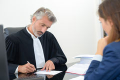 Lawyer signing document in office with female client. Lawyer signing a document in an office with female client royalty free stock photography