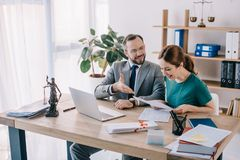 Lawyer and smiling client discussing contract at workplace with laptop. In office royalty free stock image
