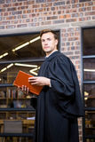 Lawyer standing near library with law book Royalty Free Stock Photos