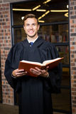 Lawyer standing near library with law book Royalty Free Stock Image