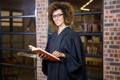 Lawyer standing near library with law book Stock Images