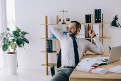 Lawyer stretching while sitting at workplace with laptop. In office stock images