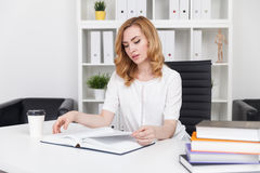 Lawyer studying case precedents. Lawyer reading book in office at her desk. Coffee and pile of folios on table. Concept of preparation to court seating Royalty Free Stock Photos