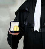 Lawyer wearing a robe holding a a justice meda. This photograph represents lawyer wearing a robe holding a a justice medal with sword and scale stock images