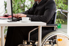 Lawyer on wheelchair. Working on laptop and driniking coffee Stock Photography