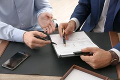 Lawyer working with client at table in office. Focus on hands stock images