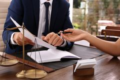 Lawyer working with client at table in office. Focus on hands royalty free stock photo
