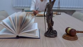 A lawyer in the workplace examines documents and legislation, the statuette of Themis with a master plan