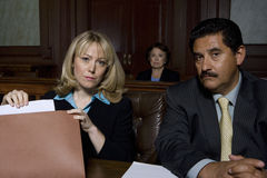 Lawyers In Courtroom. Portrait of two lawyers sitting in courtroom royalty free stock photos