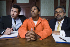 Lawyers With Criminal In Court. Two lawyers with criminal sitting in the courtroom Royalty Free Stock Photos