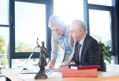 Lawyers discussing plans. Mature lawyers discussing plans at modern workplace Stock Photos