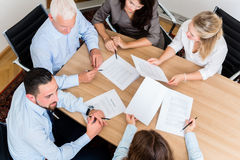 Lawyers having team meeting in law firm. Reading documents and negotiating agreements Stock Images