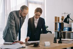 Lawyers in suits working together on project at workplace with gavel and laptop. In office royalty free stock photo