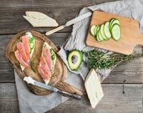 Lax-, avokado- och timjansmörgåsar i bagetten som binds upp med garneringrepet på ett lantligt träbräde över grov wood bakgrund Royaltyfria Foton