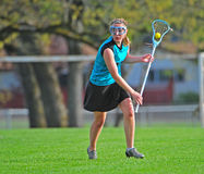 LAX player with the ball. High School girls varsity lacrosse player looking for an open team mate Stock Photography
