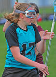 LAX player maneuvers. High School girls varsity lacrosse player maneuvering around a defensive player Royalty Free Stock Images