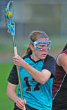LAX player portrait. High School girls varsity lacrosse player looking for an open team mate Royalty Free Stock Image