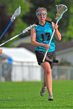 LAX player protecting the ball. High School girls varsity lacrosse player protecting her stick and the ball Royalty Free Stock Photos