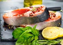 Lax Rå forellfiskbiff med örter och citronen på svart kritiserar bakgrund matlagning arkivfoto