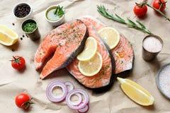 Laxbiffar med örter, kryddor och citronen som är klara för att laga mat Arkivfoton