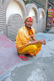 LAXMAN JHULA, INDIA - APRIL 15, 2017: Een Hindoese sadhuzitting naast de weg in Laxman Jhula Royalty-vrije Stock Foto