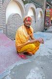 LAXMAN JHULA, INDIEN - 15. APRIL 2017: Ein hindisches sadhu, das nahe bei der Straße in Laxman Jhula sitzt Lizenzfreies Stockfoto