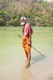 LAxMAN JHULA, INDIEN - APRIL 15, 2017: En hinduisk sadhu som rymmer ho Fotografering för Bildbyråer