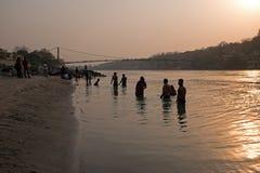 LAXMAN JHULA, INDIEN - 15. APRIL 2017: Leute nehmen ein Bad im Ganges Indien bei Sonnenuntergang Lizenzfreie Stockbilder