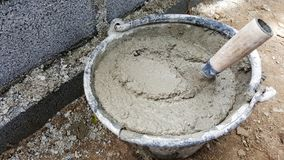 Lay bricks with cement mixing tub, mortar concrete royalty free stock photo