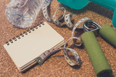 Lay Flat - Dumbbell, Measuring Tape, Hand Grip, Mineral Water &. Lay Flat - Dumbbell, Measuring Tape, Mineral Water & Blank Notebook for Motivational Quotes/ royalty free stock photos