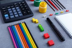 Lay-out van hun potloden en kleurpotloden, een calculator, een notitieboekje en heldere kleuren met borstels Stock Afbeelding