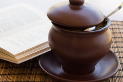 Сlay pot on a napkin with book Stock Photography