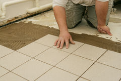 Lay a stone floor. Worker laying a stone floor on the ground stock image