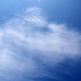 Layer of broken stratus clouds under a deep blue sky. A layer of broken stratus clouds under a deep blue sky Royalty Free Stock Image