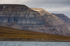 Layer cake mountains. Plateau-shaped mountains made up of horizontal layers of sedimentary rocks. Isfjorden, Longyearbyen, Svalbard, Norway royalty free stock images