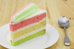 Layer cake on a white plate with a small spoon. Place on wooden table Stock Images