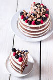 Layer cake on white wooden table and one slice on saucer. Royalty Free Stock Photos