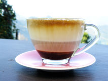 The layer of cappuccino. Hot cup of coffee, The layer of cappuccino in transparent glass with a pink plate on wooden table. Lifestyle in the morning and natural royalty free stock photo