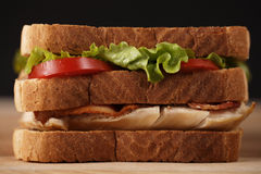 Layer chicken club sandwich. Chicken club sandwich on a wooden cutting board with very shallow depth of field royalty free stock images