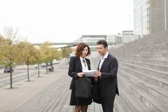 Male lawyer speaking with female client. Layer and client standing on big gray stairs. Woman hold documents about court statement in hand. Man tell about very royalty free stock photos